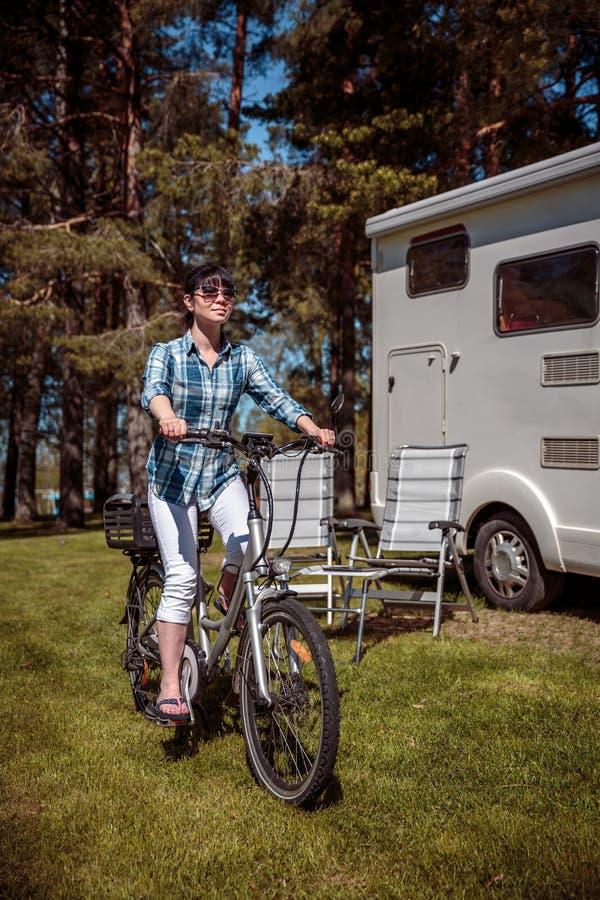 Vrouw op elektrische fiets die bij de auto Va rusten van de kampeerterreinvr Caravan royalty-vrije stock afbeeldingen