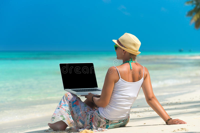 Vrouw op exotisch tropisch strand met laptop computer royalty-vrije stock afbeeldingen