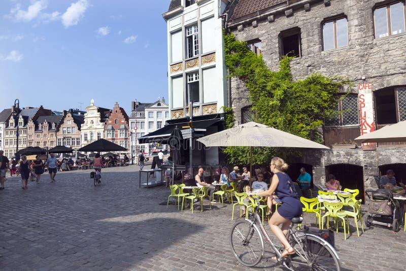 Vrouw op fiets en openluchtcafã© dichtbij groentenmarkt in centrum van royalty-vrije stock afbeelding