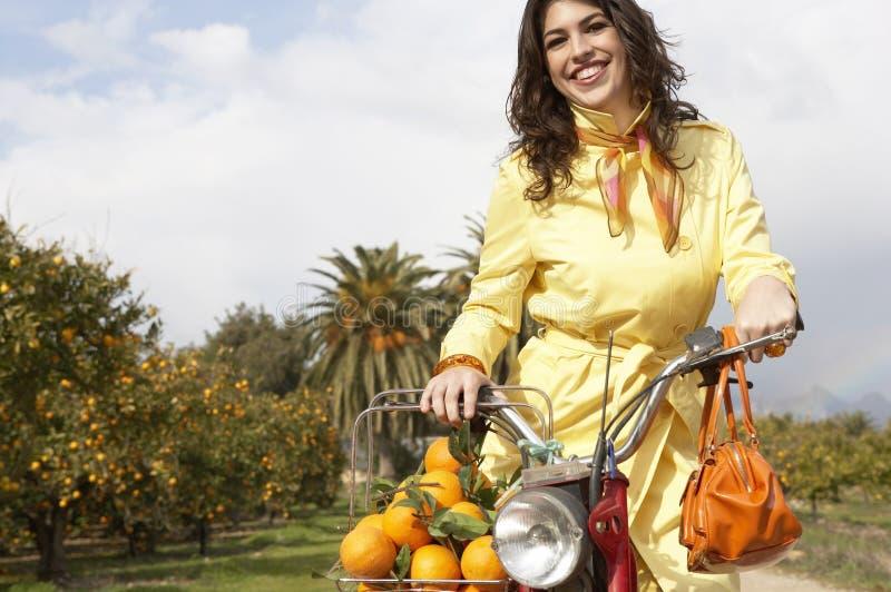 Vrouw op Fiets met Sinaasappelen stock foto