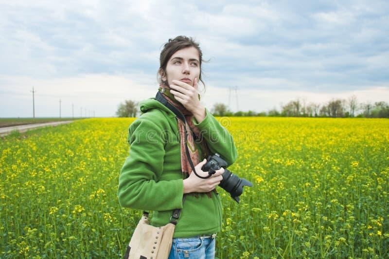 Vrouw op gebied met camera stock afbeelding