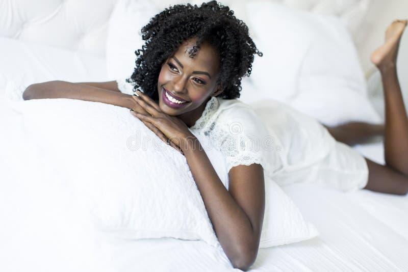 Vrouw op het bed stock foto's