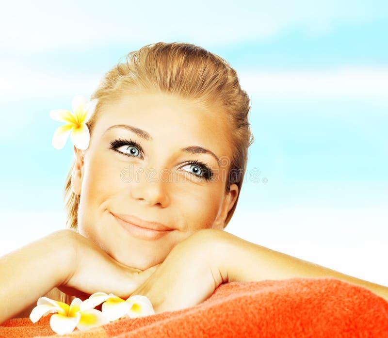 Vrouw op het bed van de kuuroordmassage op het strand royalty-vrije stock afbeelding