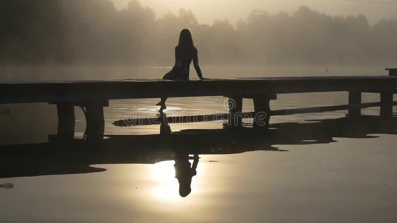 Vrouw op het dok in de mist