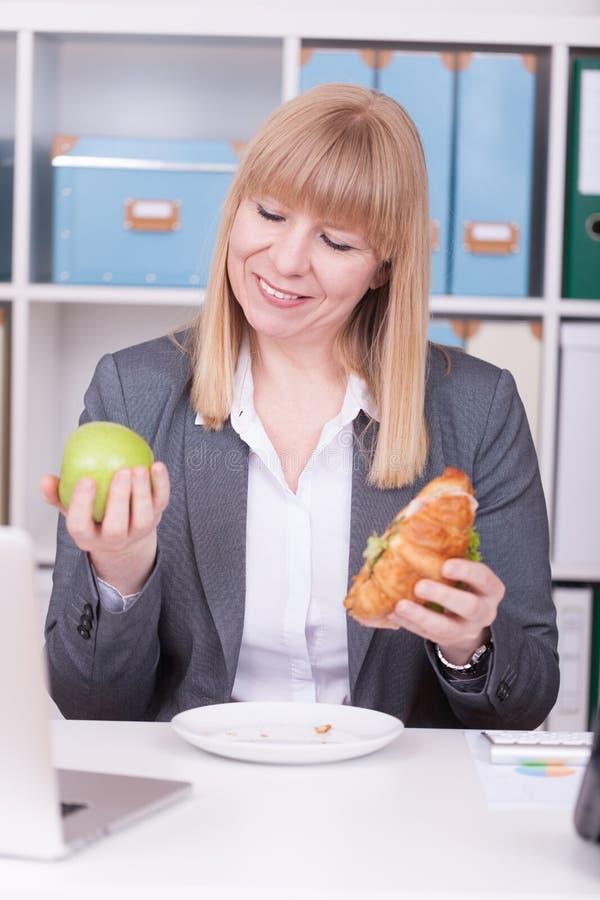 Vrouw op het kantoor die lunch hebben Concept voor healty of ongezond voedsel op het werk stock fotografie