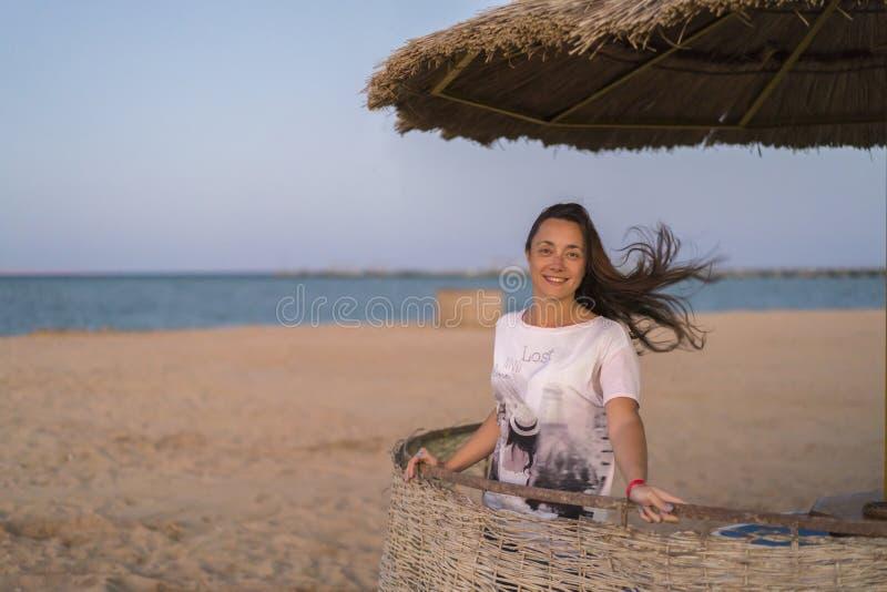 vrouw op het strand die diepe adem nemen die verse lucht van vrijheid genieten Gelukkige jonge vrouw die van zeebries genieten bi stock foto