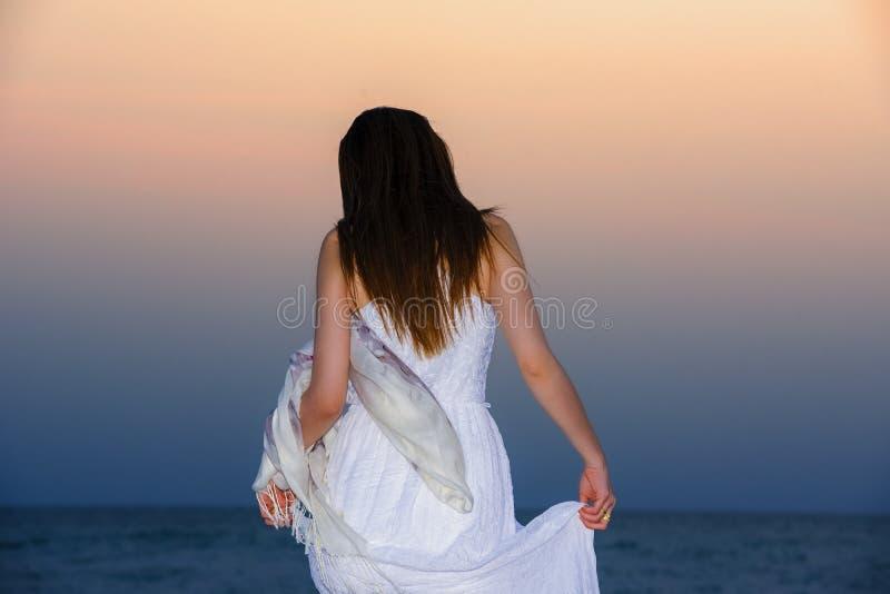 Vrouw op het strand, Jonge slanke mooie vrouw op zonsondergangstrand stock afbeeldingen