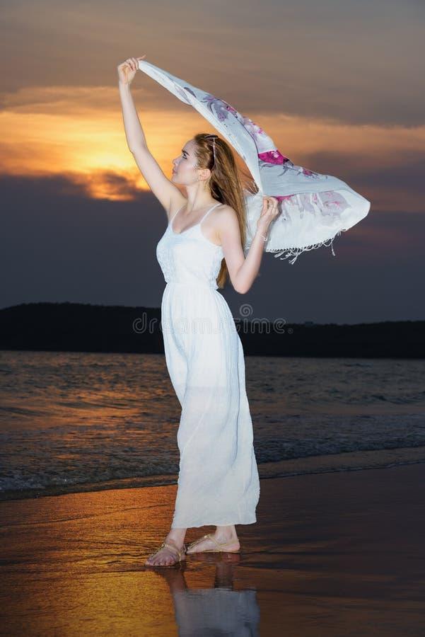 Vrouw op het strand, Jonge slanke mooie vrouw op zonsondergangstrand royalty-vrije stock foto's