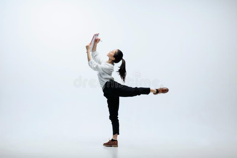 Vrouw op kantoor en geïsoleerd springen die aan studioachtergrond werken royalty-vrije stock afbeeldingen