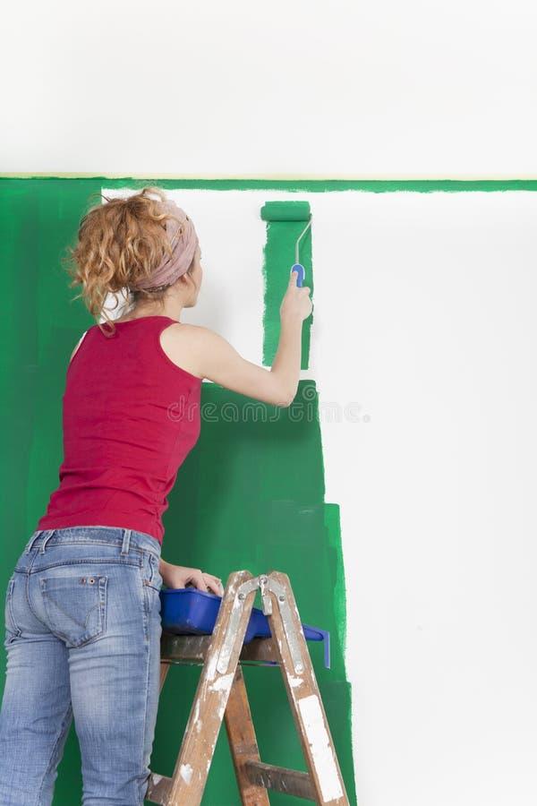 Vrouw op ladder het schilderen groene muur royalty-vrije stock foto