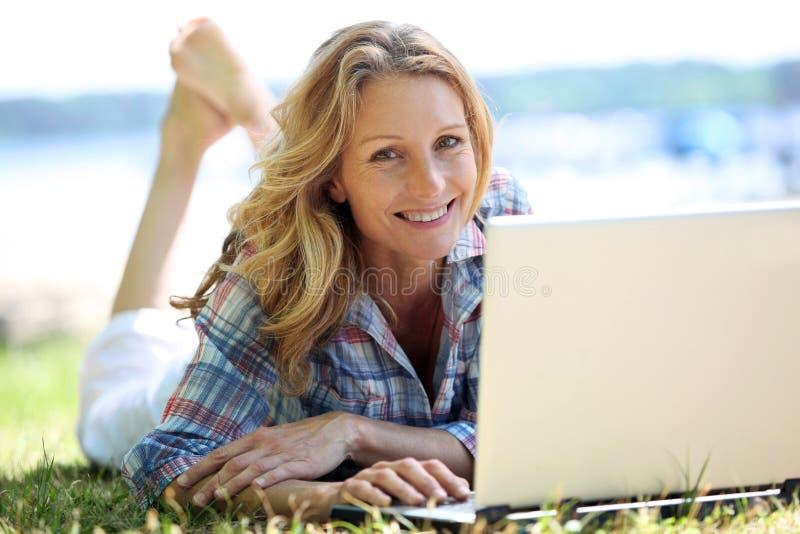Vrouw op laptop buiten royalty-vrije stock foto's