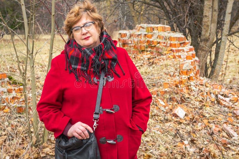 Vrouw op middelbare leeftijd met glazen en een rood jasje stock foto's
