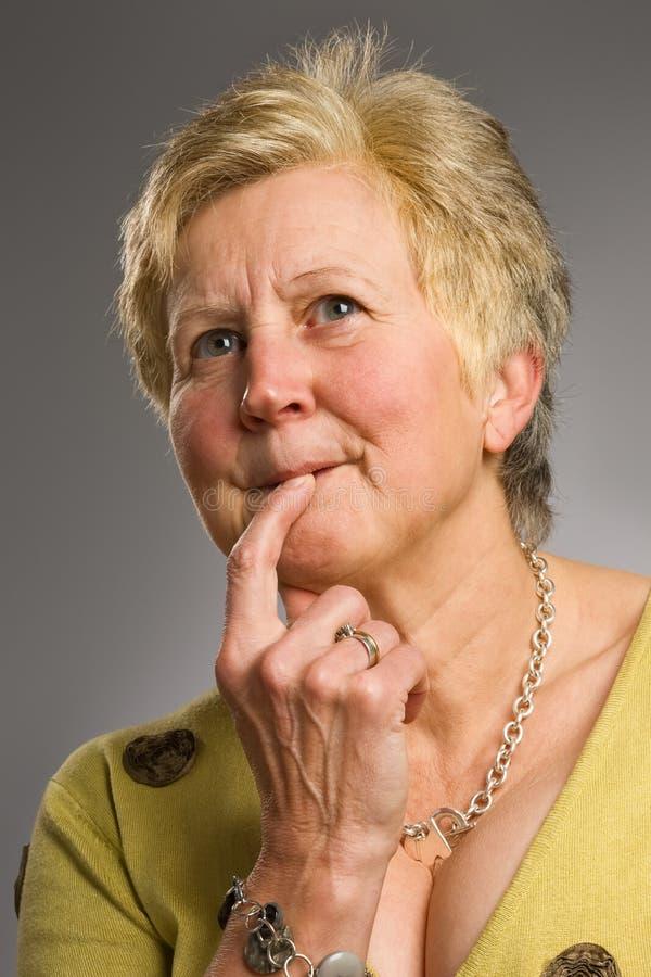 Vrouw op middelbare leeftijd met peinzende uitdrukking stock afbeeldingen