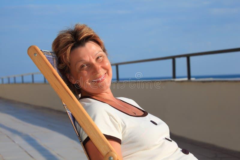 Vrouw op middelbare leeftijd in zitkamer op veranda over overzees stock foto's