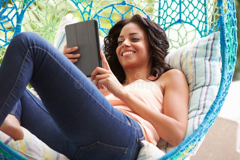 Vrouw op Openluchttuinschommeling Seat die Digitale Tablet gebruiken royalty-vrije stock fotografie