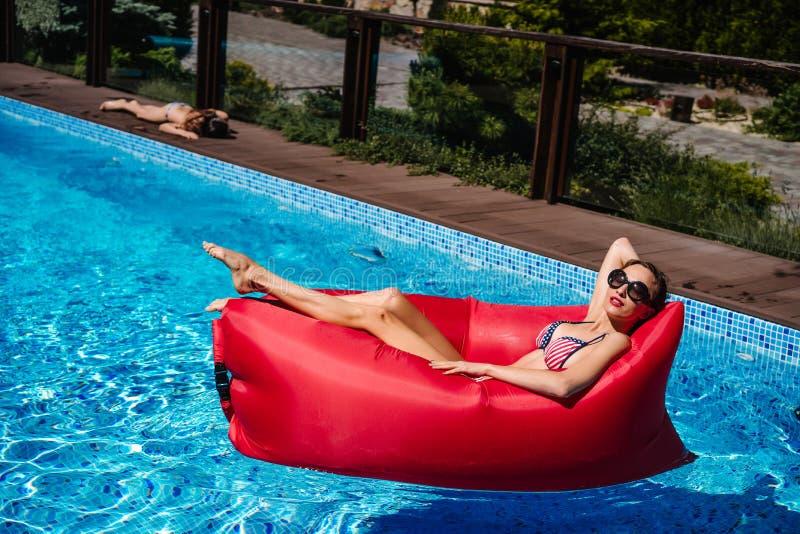 Vrouw op rode lanterfanter in pool royalty-vrije stock afbeeldingen