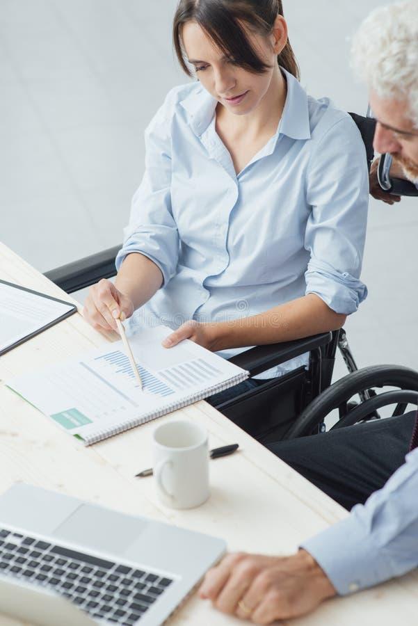 Vrouw op rolstoel die bij bureau werken stock afbeeldingen