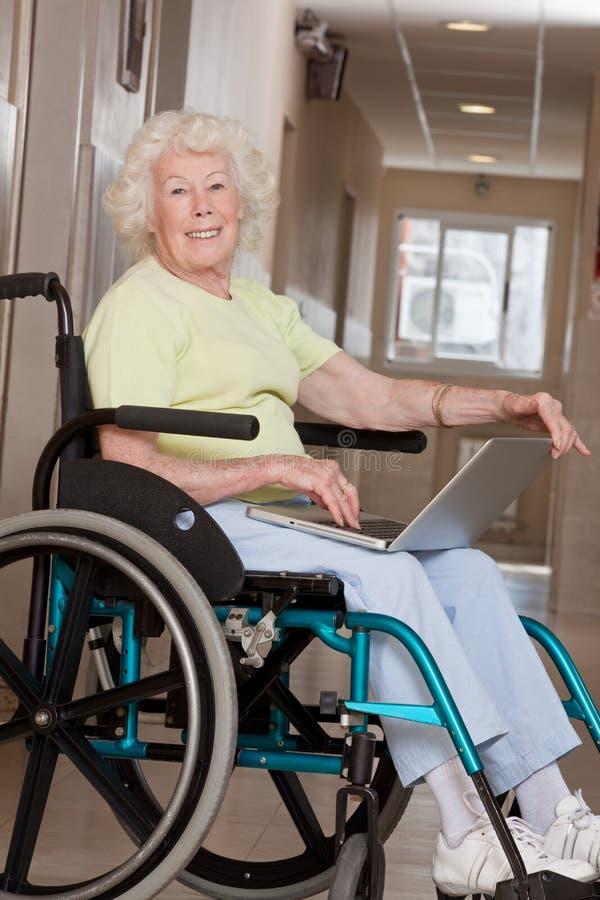 Vrouw op Rolstoel die Laptop met behulp van stock afbeeldingen