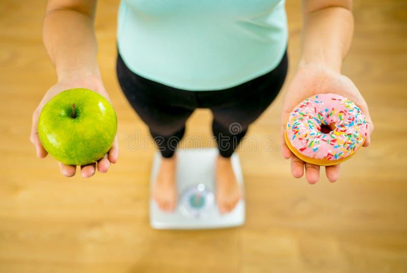 Vrouw op schaal die de appel van de gewichtsholding meten en donuts tussen gezond of ongezond voedsel kiezen royalty-vrije stock foto's