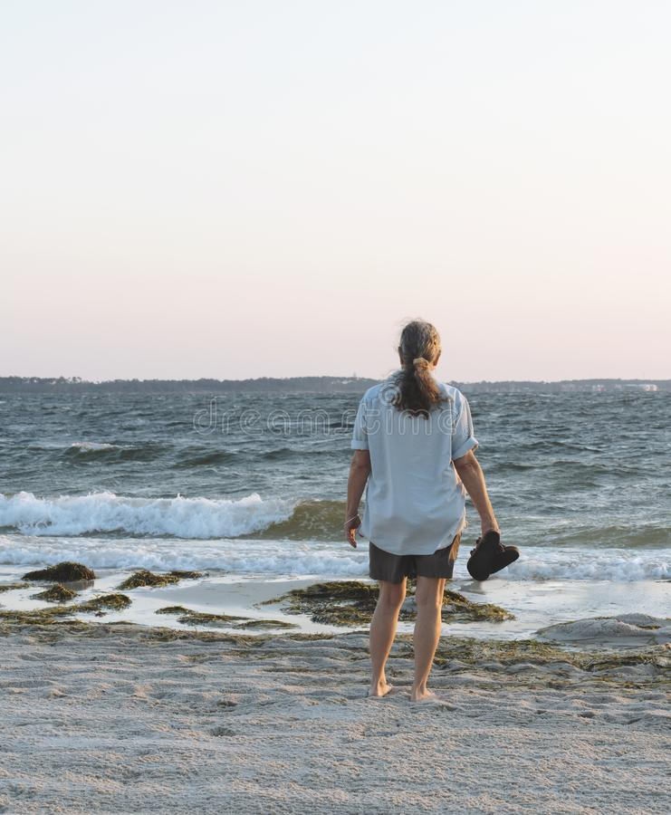 Vrouw op Strand in Dawn Gazing uit aan overzees stock foto's