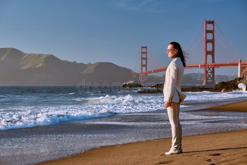 Vrouw op strand dichtbij Golden gate bridge stock afbeelding