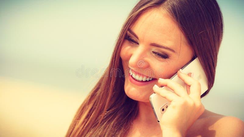 Vrouw op strand die door mobiele telefoon spreken royalty-vrije stock fotografie