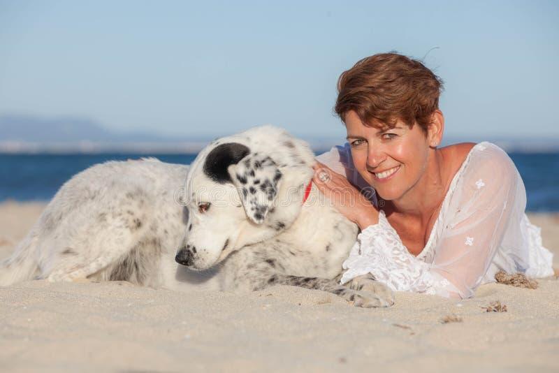 Vrouw op vakantie met huisdierenhond stock afbeelding