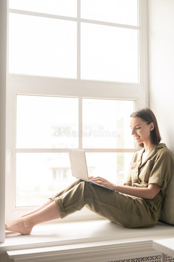 Vrouw op vensterbank stock fotografie