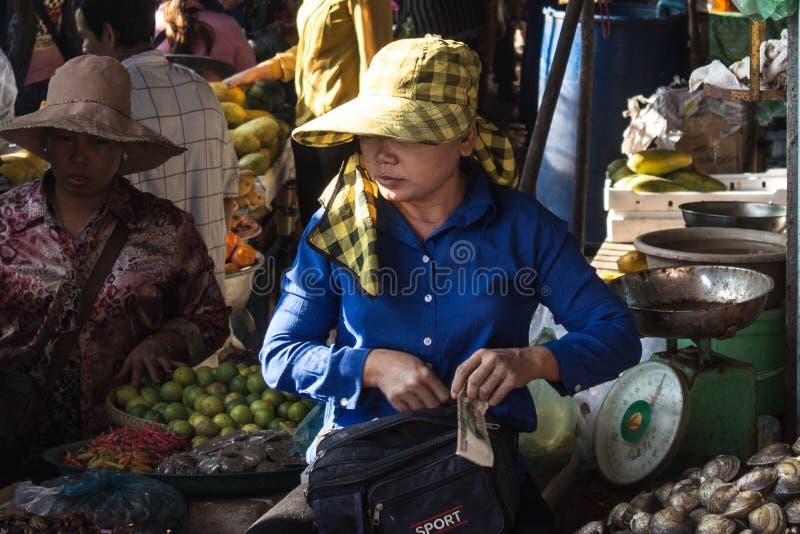 Vrouw op voedselmarkt in Kambodja die geld ontvangen stock foto