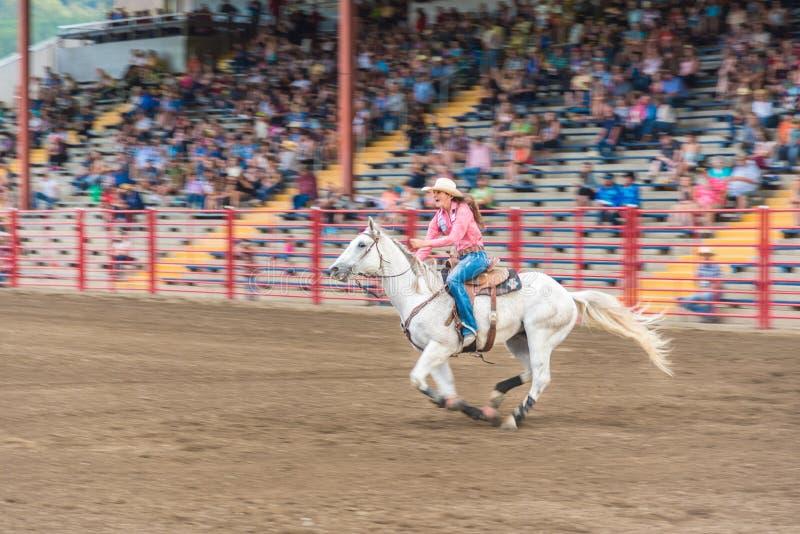 Vrouw op wit paard die bij hoge snelheid bij vat het rennen de concurrentie galopperen royalty-vrije stock fotografie