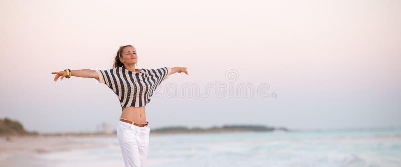 In vrouw op zeekust in zich avond het verheugen royalty-vrije stock afbeelding