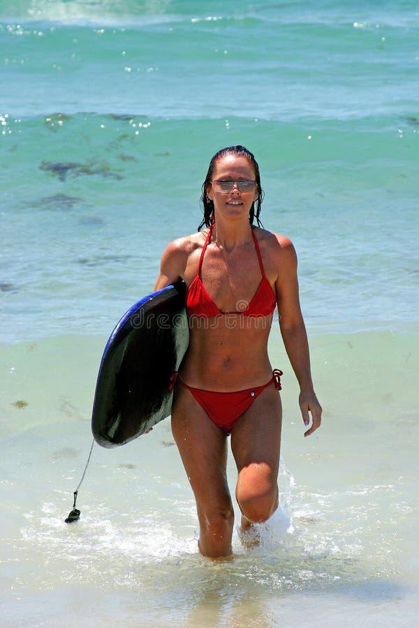 Vrouw op zonnig Spaans strand in overzees na het surfen en lichaam het inschepen royalty-vrije stock afbeelding
