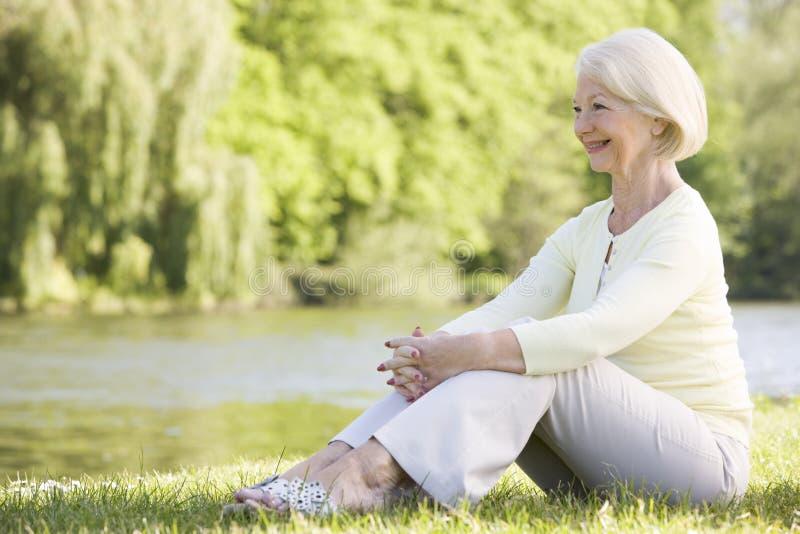 Vrouw in openlucht bij park door meer te glimlachen royalty-vrije stock afbeelding