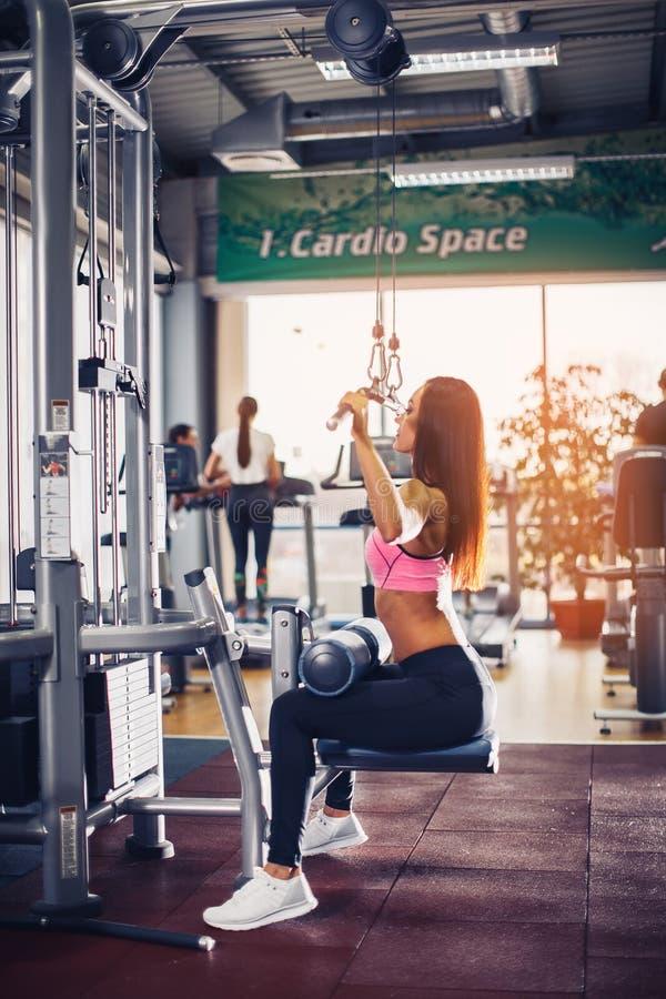 Vrouw opleiding met gewichtheffen opleidingsmachine stock afbeeldingen