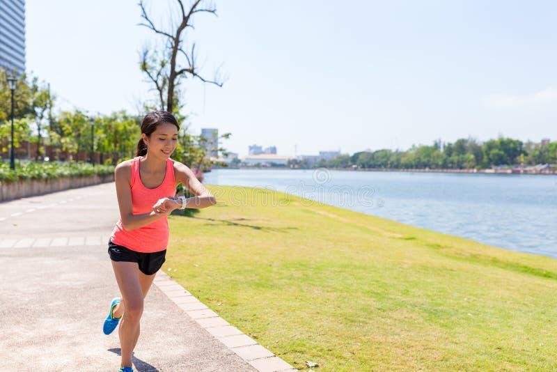 Vrouw opleiding in park en gebruik van slim horloge stock fotografie