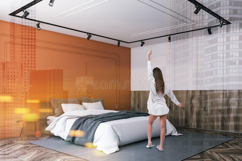 Vrouw in oranje en witte slaapkamerhoek royalty-vrije stock fotografie