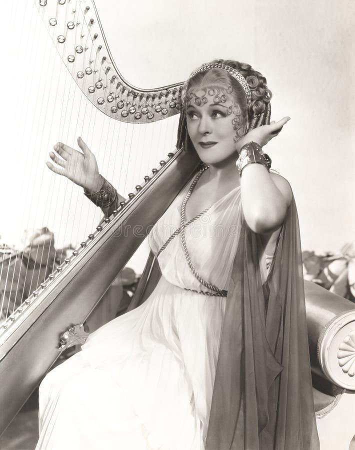 Vrouw in oude Griekse kostuum het spelen harp stock foto's