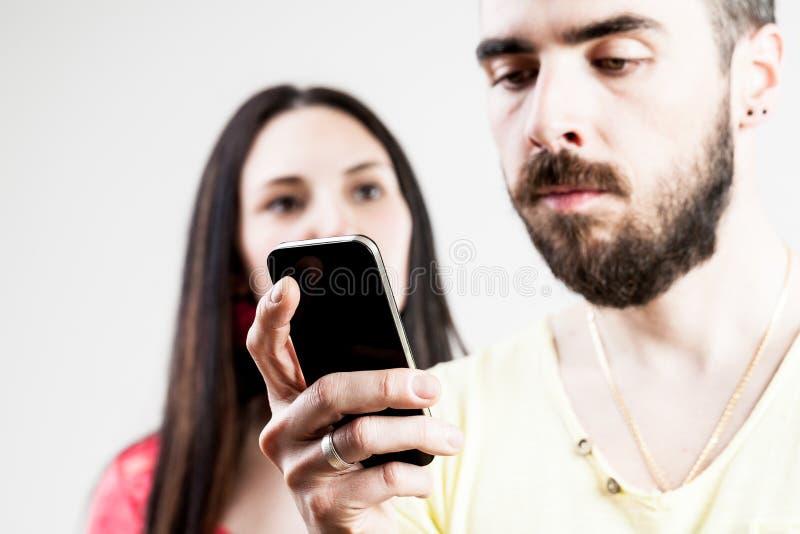 Vrouw over de zijn mens die op zijn mobiel wordt teleurgesteld stock foto