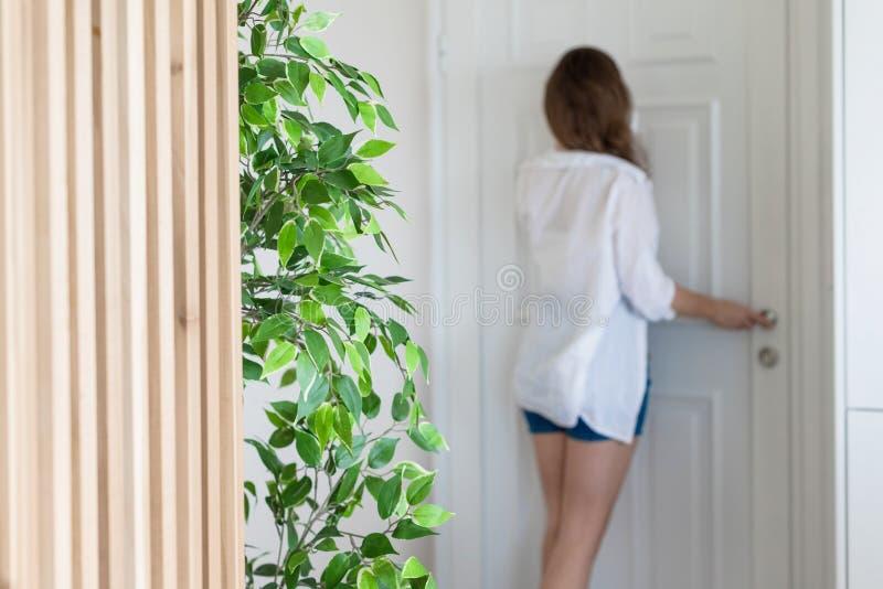 Vrouw in overhemd en borrels die in kijkglasdeur kijken wanneer somebody de deurbel belt royalty-vrije stock foto's