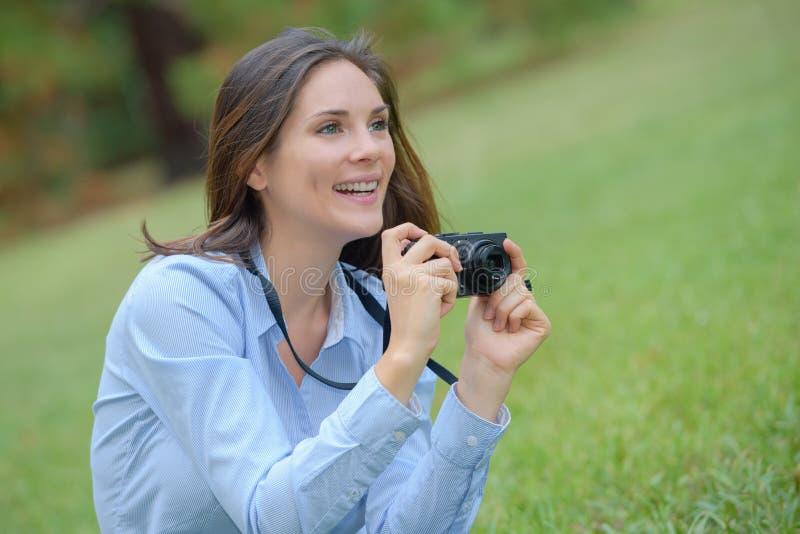 Vrouw in park die foto nemen stock afbeeldingen