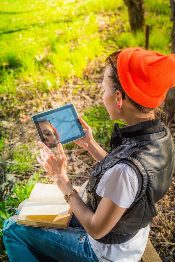 Vrouw in park openlucht met tablet en boek stock fotografie