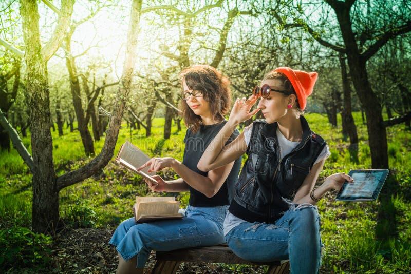 Vrouw in park openlucht met tablet en boek stock afbeelding