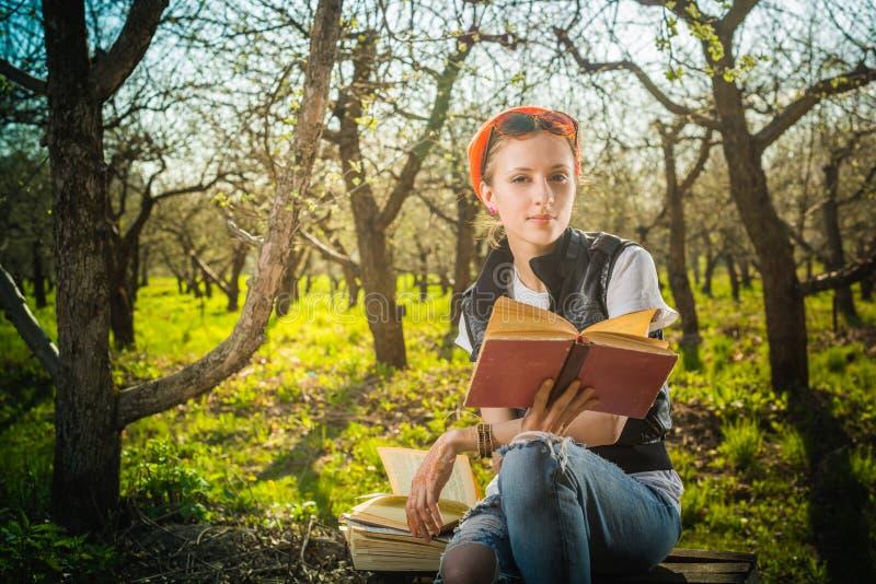 Vrouw in park openlucht met tablet en boek royalty-vrije stock afbeeldingen