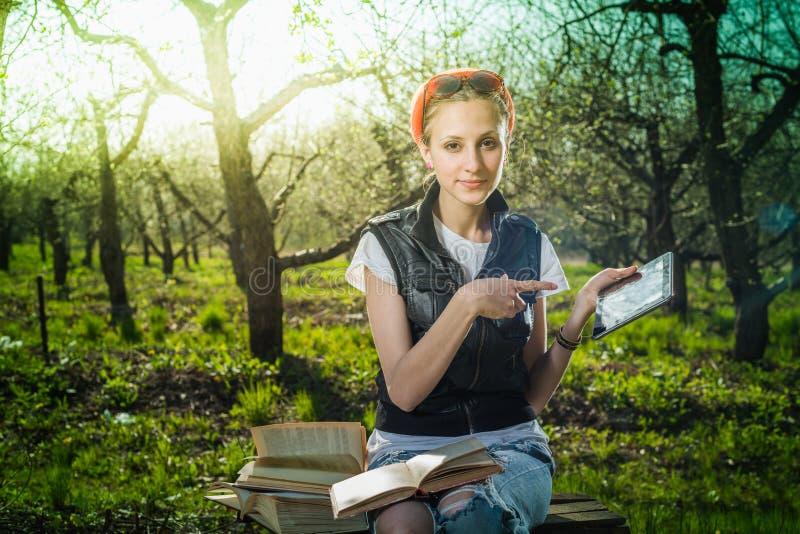 Vrouw in park openlucht met tablet en boek stock foto