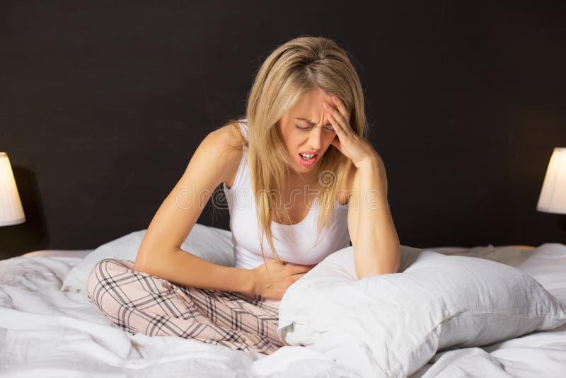 Vrouw in pijnzitting in bed stock fotografie