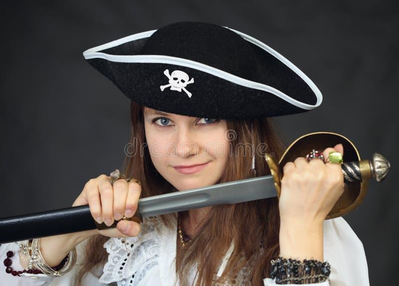 Vrouw - piraat die sabel van een schede krijgt royalty-vrije stock afbeeldingen