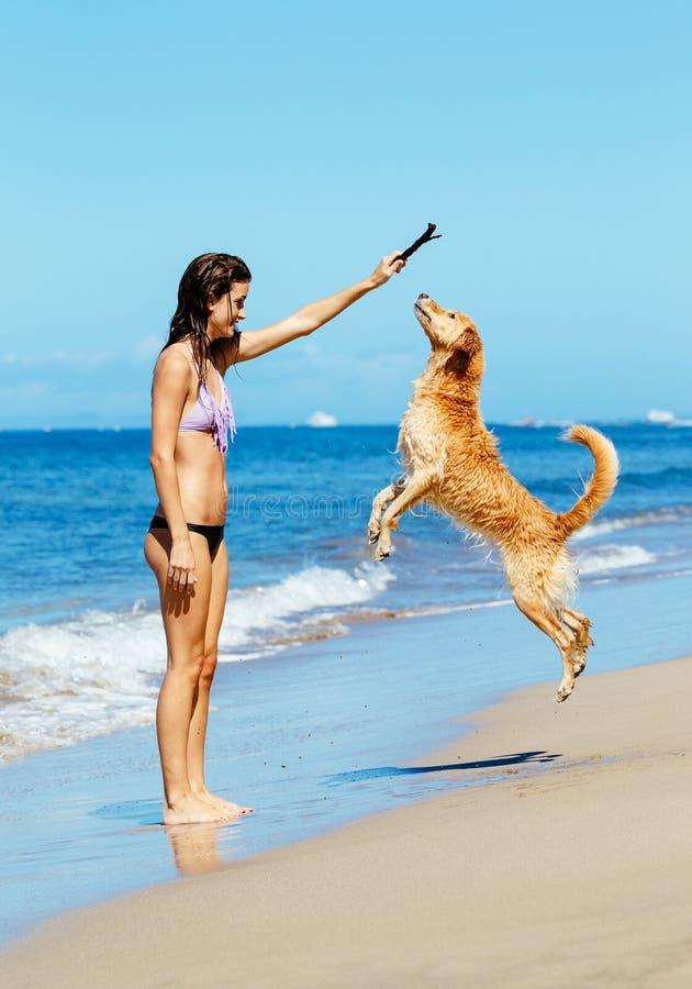 Vrouw Playiing die met Hond in de Lucht springen stock fotografie
