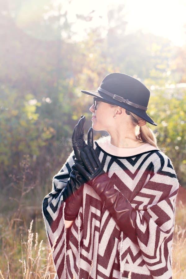 Vrouw in poncho, hoed en lange handschoenen royalty-vrije stock foto's
