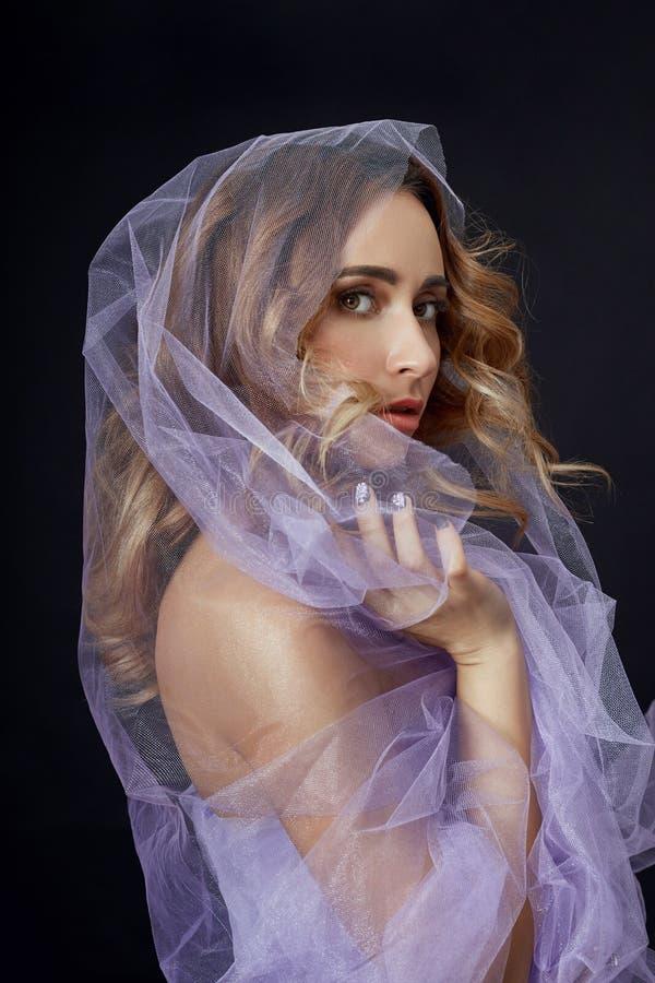 Vrouw in purpere stof, mooi slank cijfer, zuiverheid en integriteit wordt verpakt die Perfect gezicht skincare, natuurlijke schoo stock fotografie