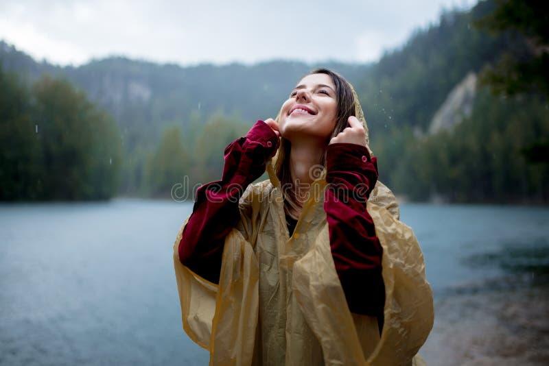 Vrouw in regenjas dichtbij meer in regenachtige dag stock foto's